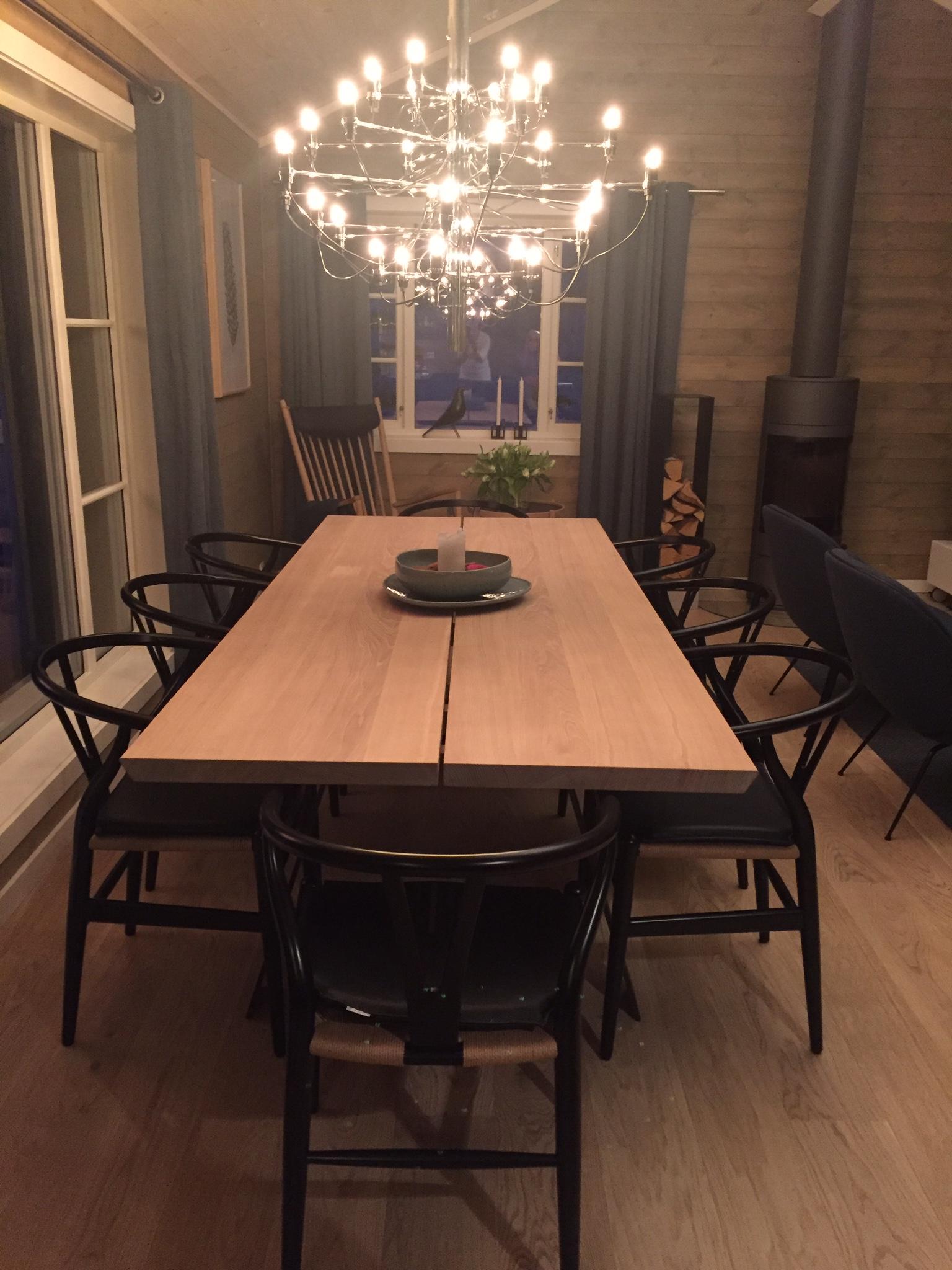 Plank heltre spisebord fra Naver, sorte Y-stoler designet av Hans J. Wegner og lysekronen er fra Flos.